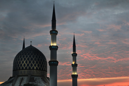 Silhouette of a mosque structure with red dawn skies in background