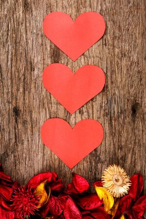 potpourri: Hearts with red potpourri flower petals on wooden background