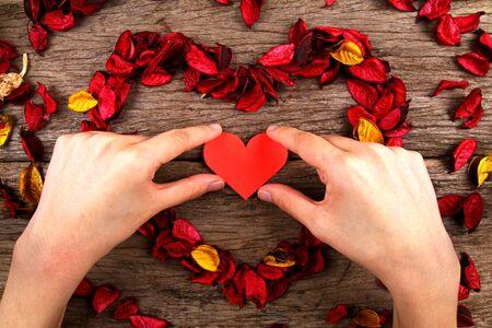 potpourri: Hand placing heart in centre of red potpourri heart