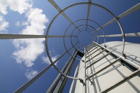 caged: Sky view from a caged ladder of industrial structure Stock Photo