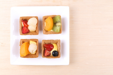 mini oven: Assorted fruit tarts on a plate Stock Photo