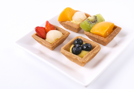 mini oven: Assorted fruit tarts on a plate isolated on white Stock Photo