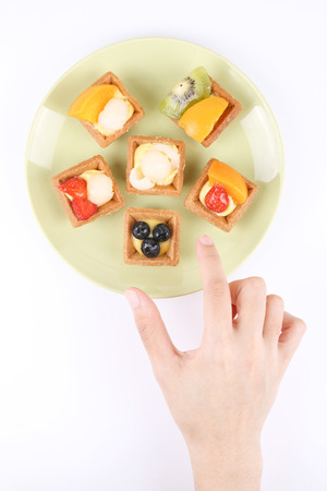 reaching out: Hand reaching out to a plate of assorted fruit tarts Stock Photo