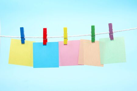 Colorful clothes pegs holding colorful notes against blue background