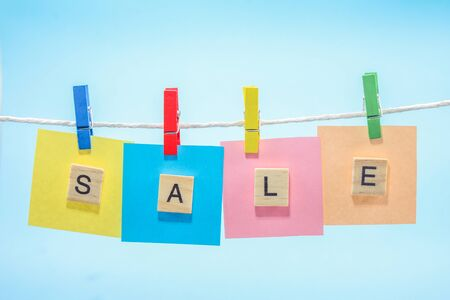 pegs: Colorful clothes pegs holding Sale sign