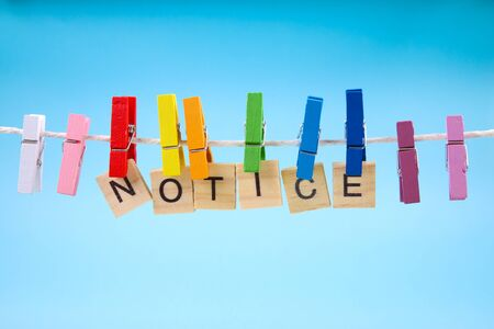 Colorful clothes pegs holding Notice sign