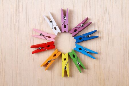 pegs: Colorful clothes pegs arranged in a circle on wooden surface