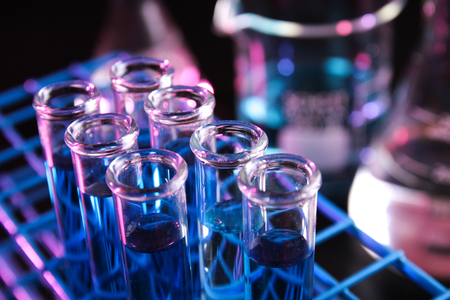 laboratory labware: Test tubes filled with blue chemicals in dark lab