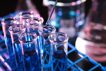 laboratory labware: Reagent dropped into test tube containing blue chemicals