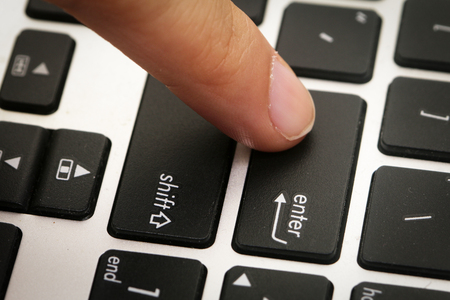 pressing: Finger pressing on ENTER button Stock Photo