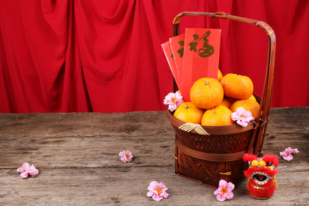 Basket of mandarin oranges with Chinese New Year decorations Фото со стока