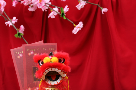 Mini lion head with Chinese new year red packets on red background