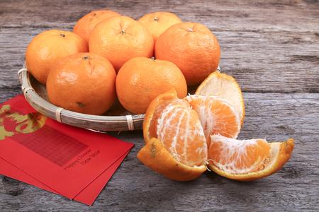 Gepelde mandarijn sinaasappelen met Chinese nieuwe jaar rode pakketten