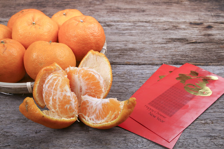 Peeled mandarin oranges with chinese new year red packets