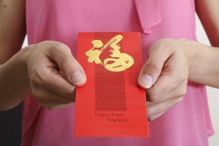 Holding Chinese New Year angpow money envelope 版權商用圖片