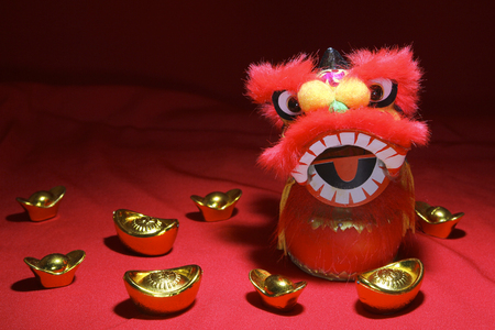 Mini chinese lion head under focus light with gold ingot decoration