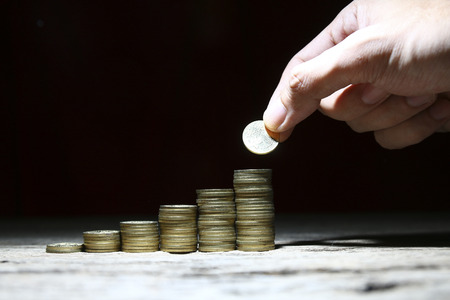 money management: Stack on coins on wooden surface with hand placing coin showing growth Stock Photo