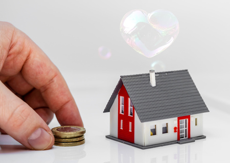 concept image dream of a house - hand putting money next to a model house Stock fotó