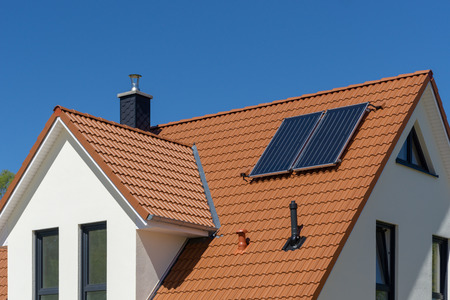 Red tiled roof of a new house with solar thermal power plant