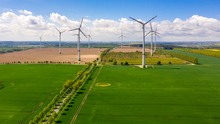 aerial view of agricultural fields with windmills or turbines