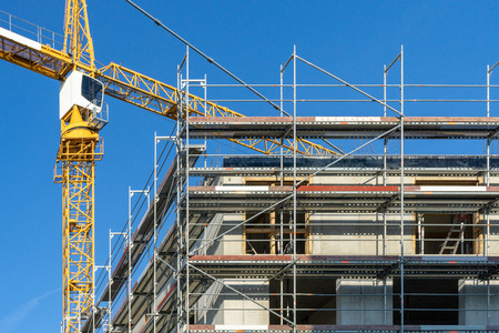 Construction site with a scaffolding at the outside and crane in the background Zdjęcie Seryjne