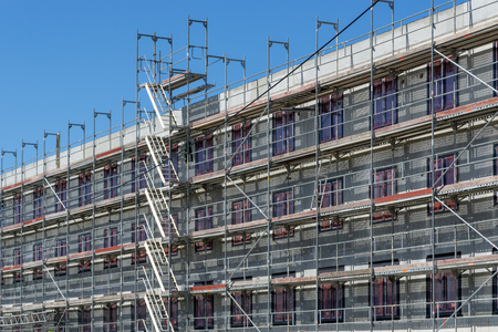 Construction site of a building with scaffolding at the outside facade Zdjęcie Seryjne