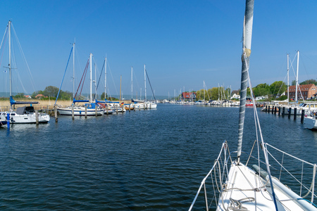 Sailing boat at the entrance of a small harbor - sunny day, no clouds