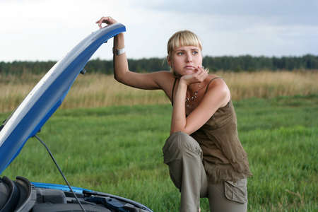 young blond woman with her broken car. The girl is sad photo