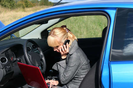 young blond woman with red notebook in a blue car. She is smiling photo