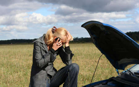 young blond woman with her broken car. The girl is crying photo