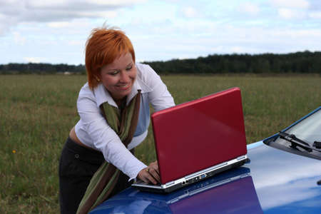 cowl: young woman with red notebook on cowl of blue car