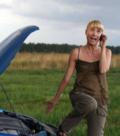 young blond woman with her broken car. The girl is angry Stock Photo - 5669379