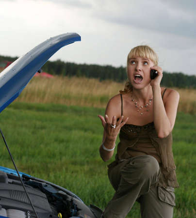 young blond woman with her broken car. The girl is angry photo