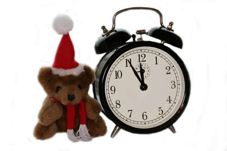 teddy bear in christmas red cap and old alarm clock photo