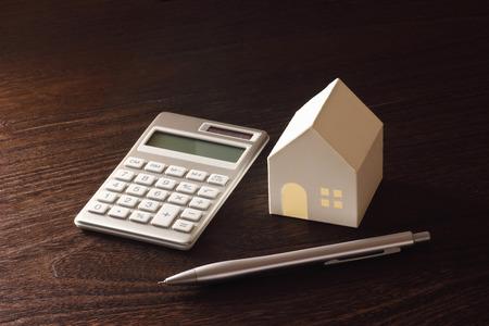 おもちゃの家とテーブルの上の電卓