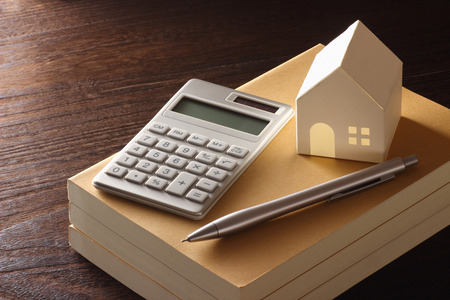 speelgoed huis en calculator op de tafel Stockfoto