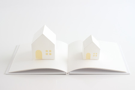 toy house: toy house and white book on the white background Stock Photo