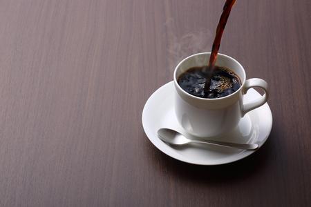 versando il caffè sul tavolo di legno
