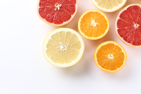 Fresh citrus fruits half cut, white background with copy space, from above