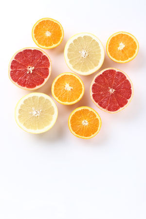 Fresh citrus fruits half cut, white background, from above