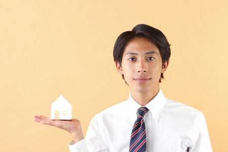 asian businessman showing a model of house