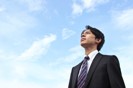 A businessman looking up at the sky