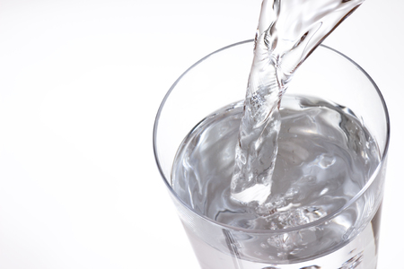 pouring water on white background 写真素材