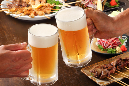 Japanese young people hands toasting and cheering beer mugs