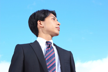 Young asian businessman looking up at the sky