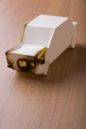 Broken paper car on wooden table