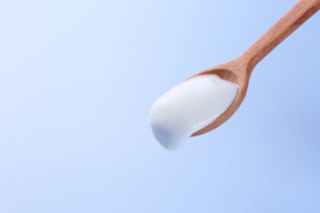 Spoon with yogurt on a blue background