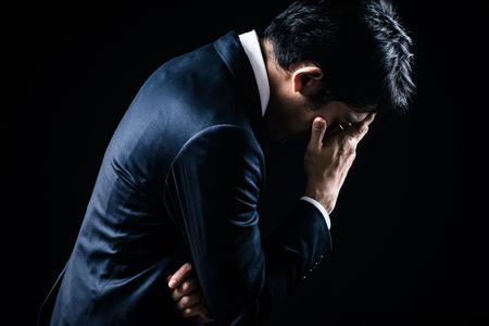 A depressed businessman on black background