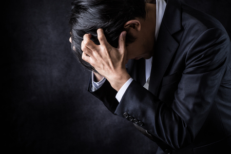 A depressed businessman on black background