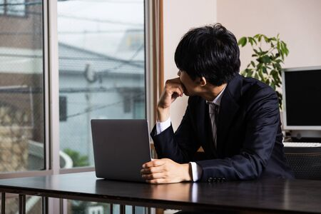 Tired Asian businessman sitting at the desk in his office